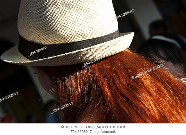 Back view of a red headeaded woman with a straw hat