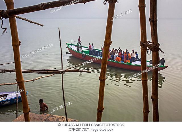 Pilgrims in a boat sailing and praying, in Ganges river, Varanasi, Uttar Pradesh, India
