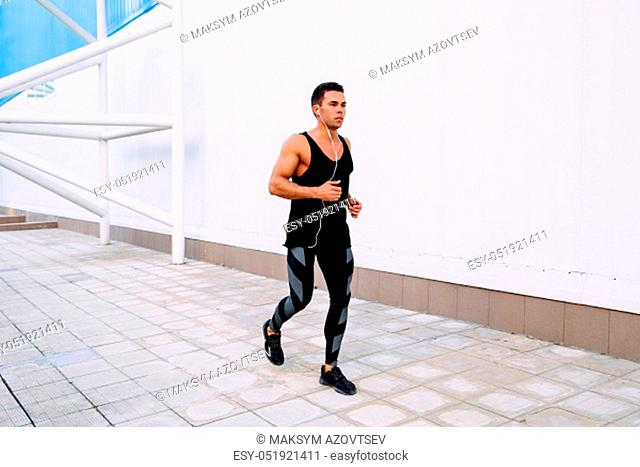 Handsome sportive man listening to music in earphones while running outdoors. Sport concept