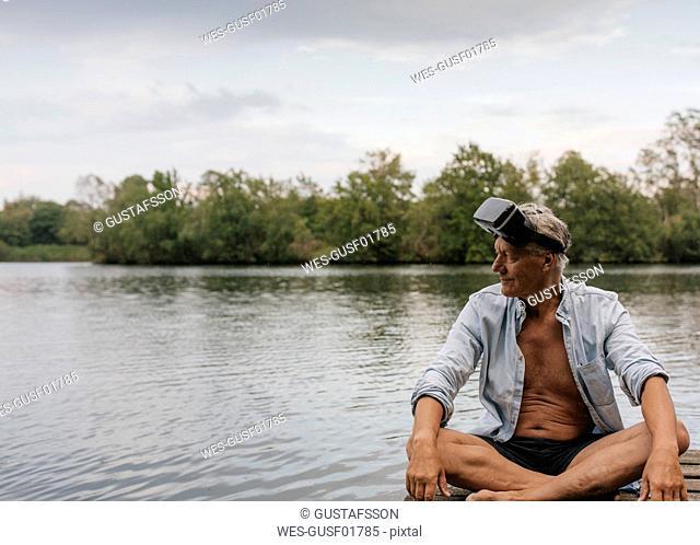 Senior man sitting on jetty at a lake wearing VR glasses