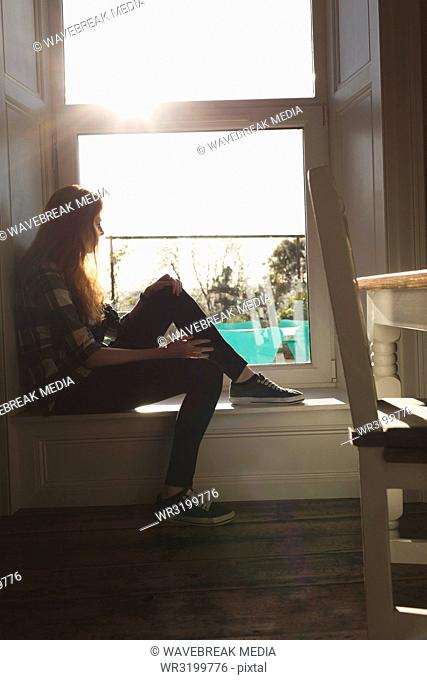 Woman siting near window at home