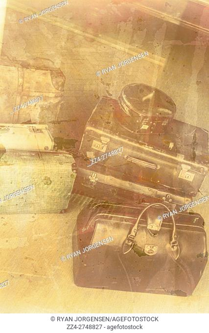 Old vintage photo on a stack of antique war time luggage reflected in the glass of a departure terminal. Nostalgic farewell