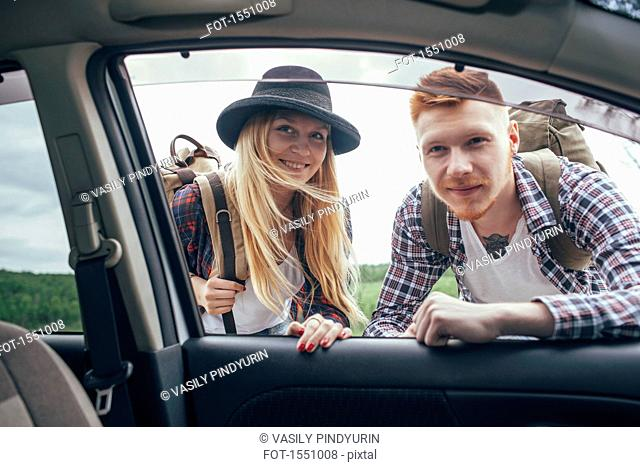Smiling male and female backpackers looking into car window