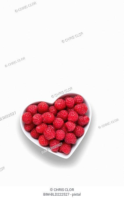 Raspberries in heart-shape bowl on white background