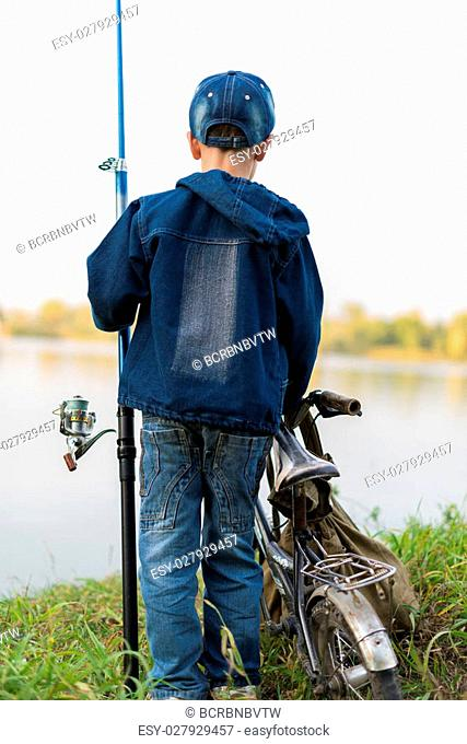 The child is traveling down the river on a bike with a fishing rod in summer