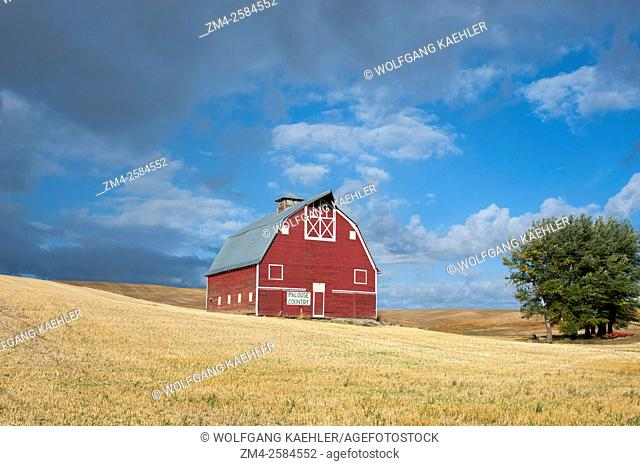 Clouds over a harvested wheat field with a red barn (Palouse Barn) in the fall near Pullman in Whitman County in the Palouse, Washington State, USA