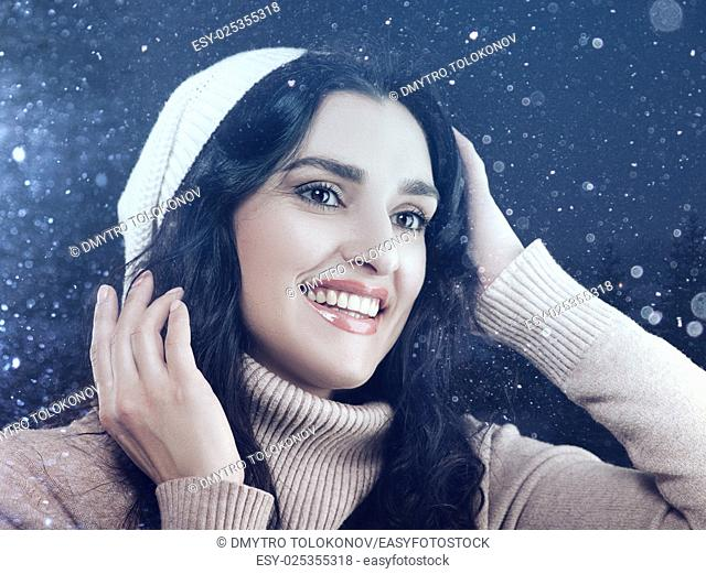 Beauty white woman dressed in winter hat and sweater, posing agaist snowfall