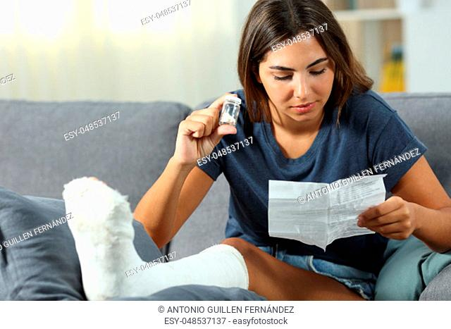Disabled woman reading pills leaflet sitting on a couch in the living room at home
