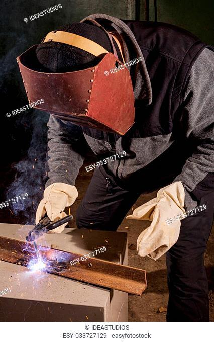Welder working in a factory welding the metal