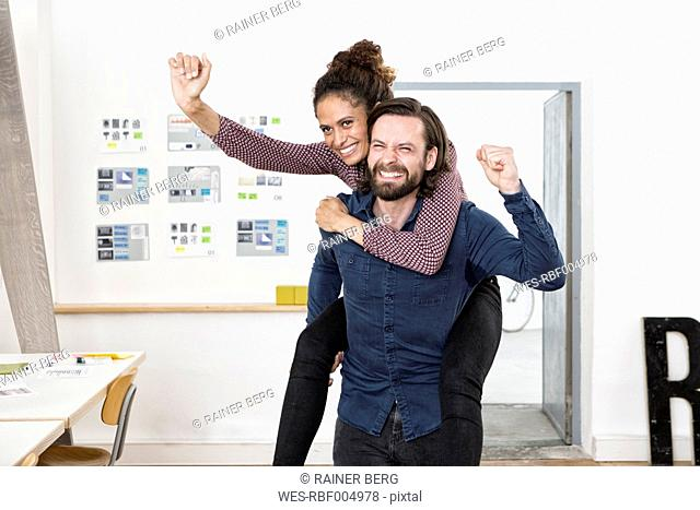 Man carrying happy woman piggyback in office