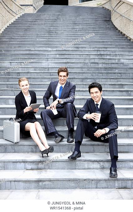 three business people sitting on the stairs together
