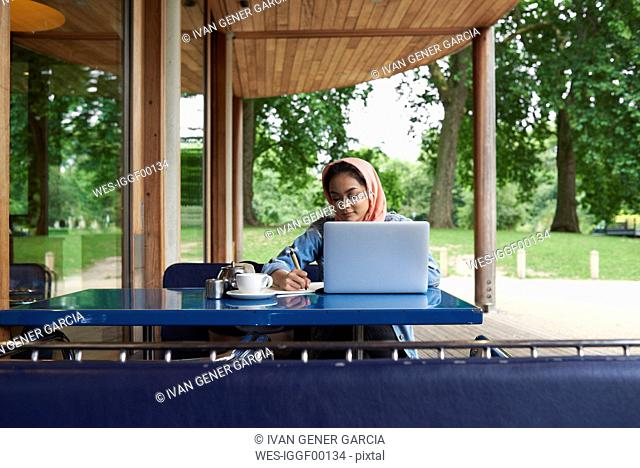 Young woman wearing hijab studying with her laptop on a terrace of a cafe
