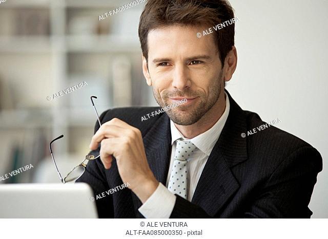 Executive holding glasses, portrait