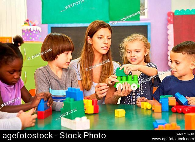 Gruppe Kinder im Kindergarten beim Spielen mit Bausteinen zusammen mit einer Erzieherin