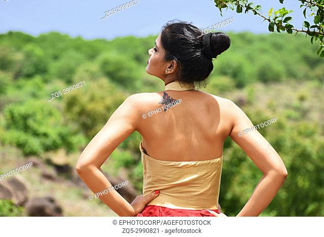 Young woman back profile with tattoo on shoulder