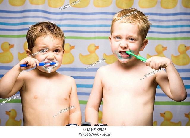 Two boys brushing teeth in bathroom sink