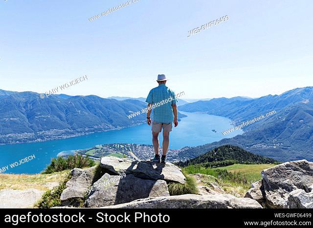 Hiker at Cimetta mountain top looking towards Lago Maggiore and Ascona, Locarno, Ticino, Switzerland