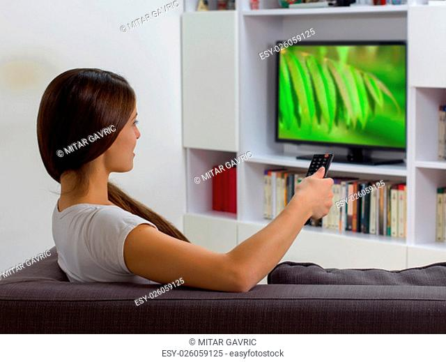 Young woman with remote control, watching TV program at home, Photo on television is from my gallery