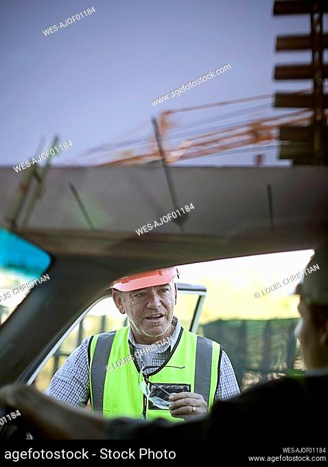 Two male construction workers chatting¶ÿby car