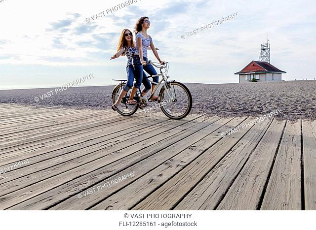Two girls riding double on a single bike on a beach boardwalk; Toronto, Ontario, Canada