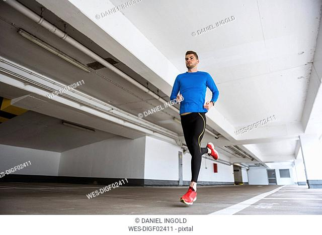 Young man running in a parking garage