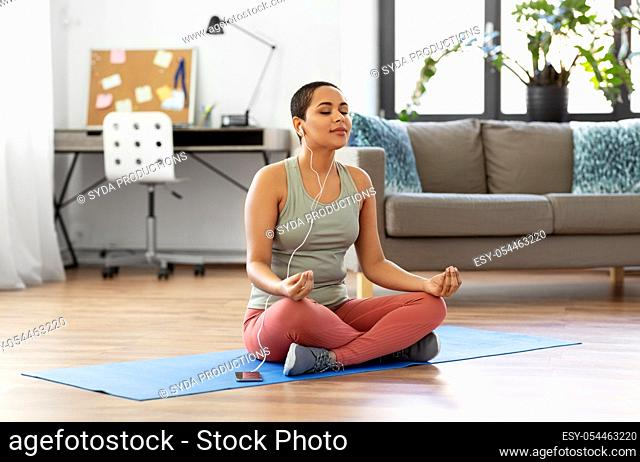 woman listening to music and meditating at tome