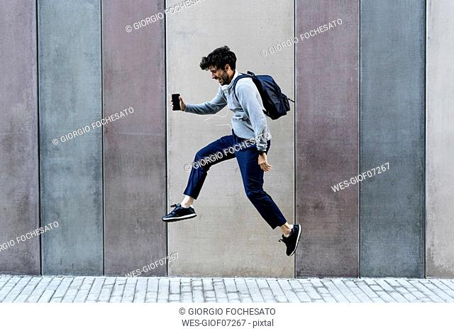 Happy man holding cell phone jumping in front of a wall