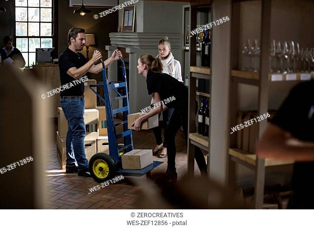 Wine staff with hand truck with boxes of wine stock in wine shop
