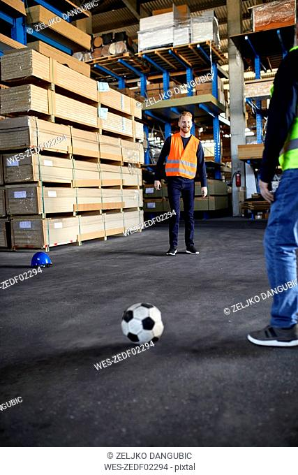 Workers playing football in factory warehouse