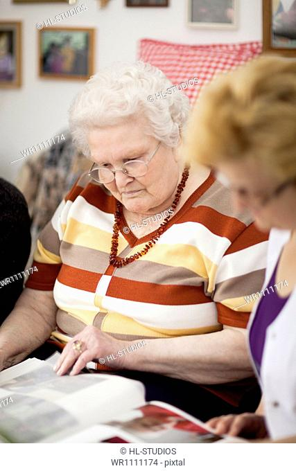 Geriatric nurse and old woman looking into photo album