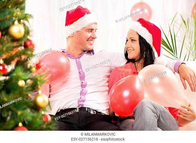 Beautiful happy Christmas couple in home with balloons