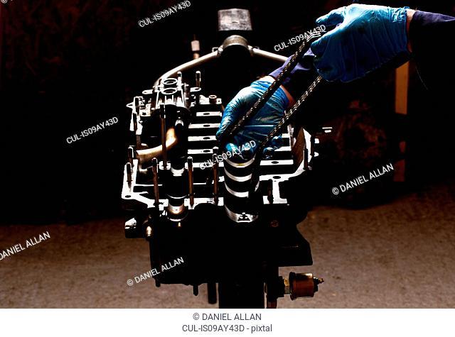 Male mechanic repairing car engine, holding cam chain