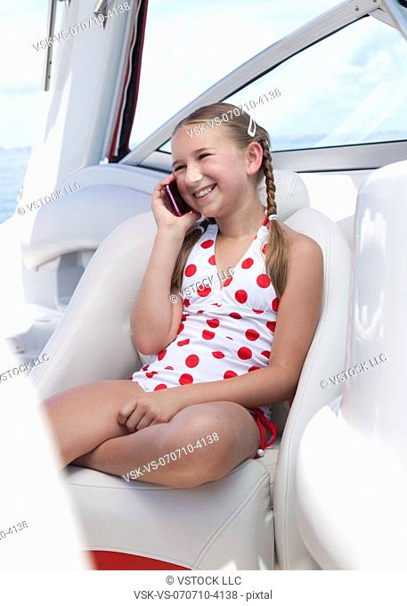 USA, Florida, St. Petersburg, Smilling girl 10-11 talking on mobile phone on yacht
