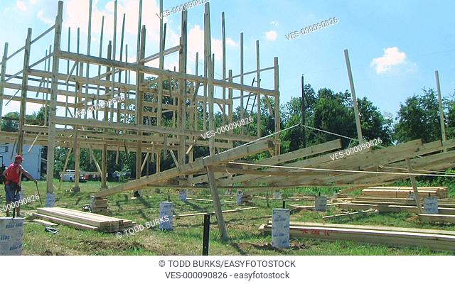 Carpenters working on building and raising a barn