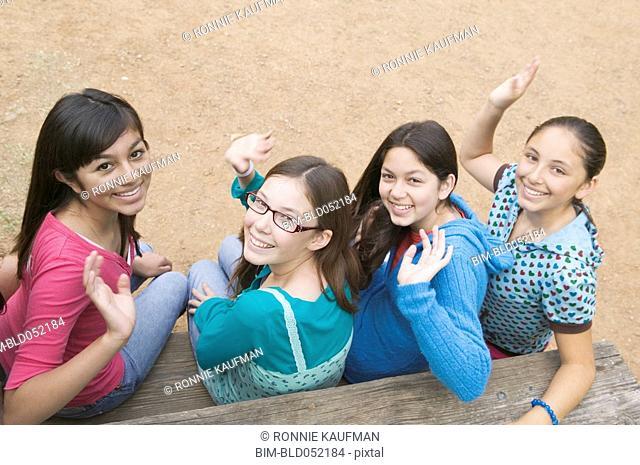 Hispanic teenaged girls waving