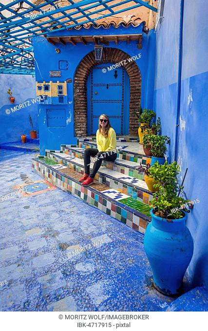 Young woman in the old town sits on a staircase, blue house walls, medina of Chefchaouen, Chaouen, Tangier-Tétouan, Kingdom of Morocco