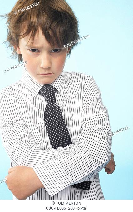 Young boy indoors wearing shirt and tie looking stern