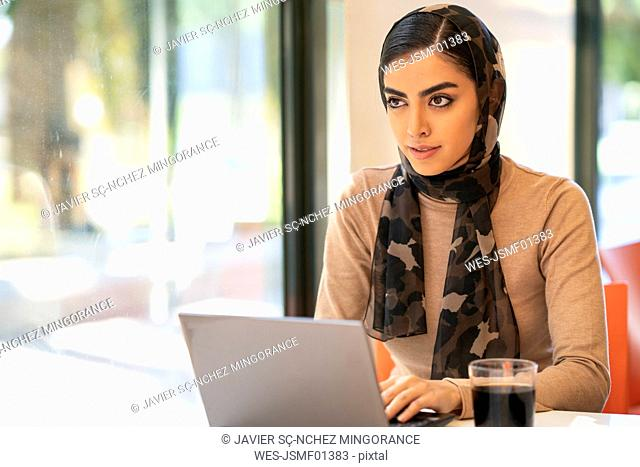 Young woman wearing headscarf using laptop in a cafe