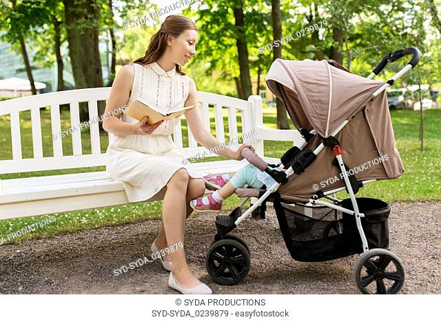 mother with child in stroller reading book at park