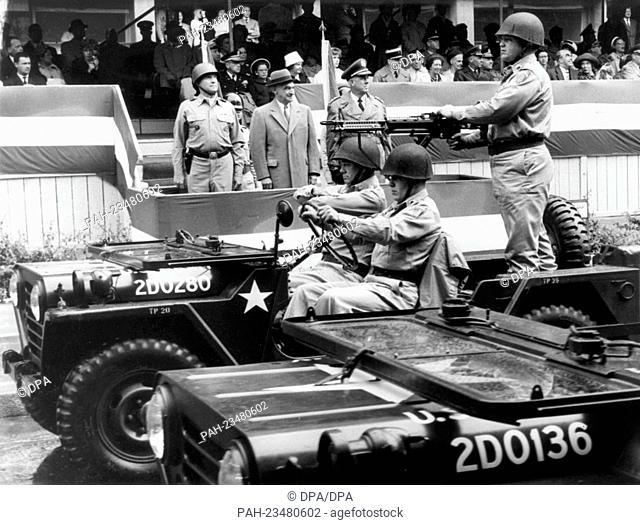 Jeeps of the US Army, equipped with heavy machine guns, driving past a VIP stand during a parade on occasion of the American Independence Day on 4th July 1962...
