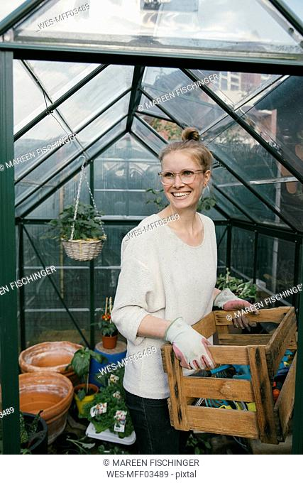 Portrait of smiling young woman with box of gardening tool in front of greenhouse