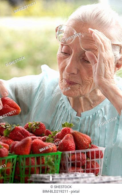 Older Caucasian woman examining strawberries at farmers market
