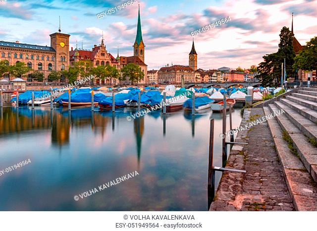 Famous Fraumunster, Church of St Peter and boats with their reflections in river Limmat during morning blue hour in Old Town of Zurich