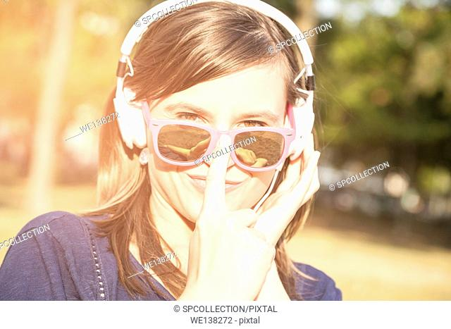 Woman with white headphones and pink sunglasses