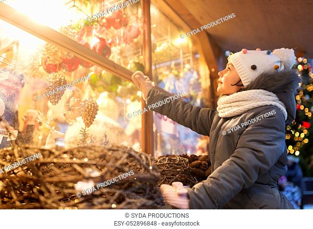 girl choosing christmas decorations at market