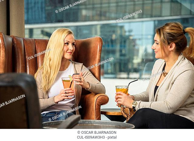 Mid adult women in bar sitting in leather armchairs face to face holding cocktails smiling