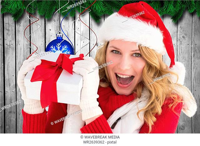 Excited woman in santa hat holding christmas gift