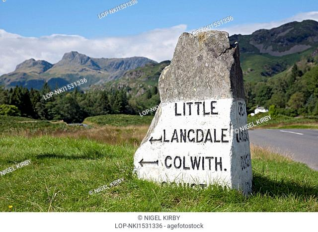 England, Cumbria, Elterwater. Stone road sign near Elterwater with Langdale Pikes in the background