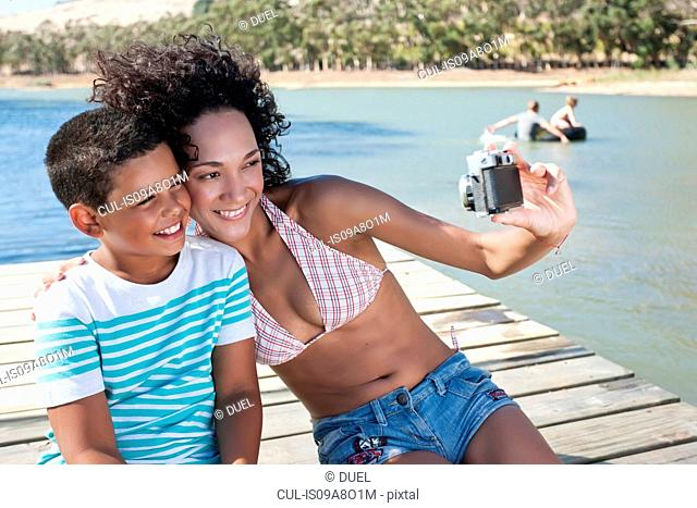 Woman taking self portrait photo with boy sitting on jetty
