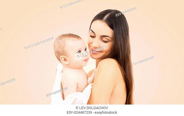 family, motherhood, parenting, people and child care concept - happy mother holding adorable baby over beige background